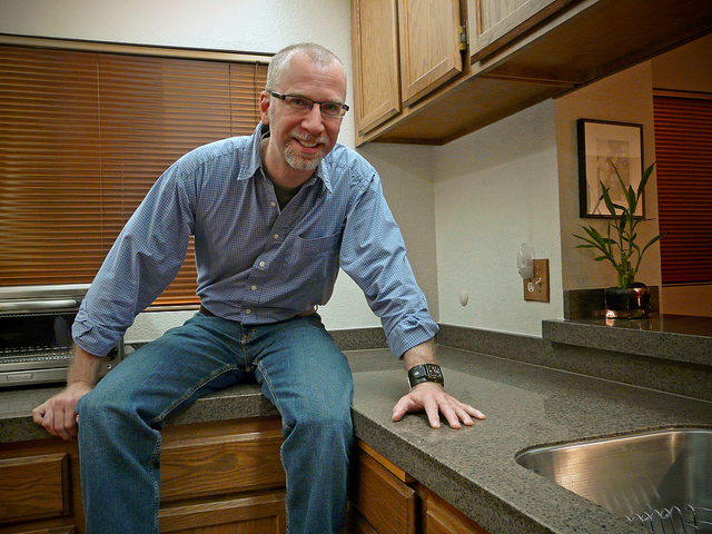 Smiling man sits in newly renovated kitchen